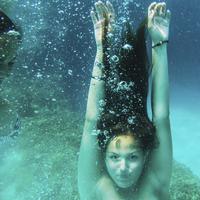 Woman diving underwater in the ocean.