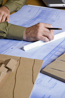 Close up of an architect working on a blue print.