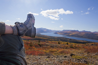 Legs and boots of hiker resting in alpine tundra coloured yellow and red by fall overlooking Fish Lake near Whitehorse, Yukon Te
