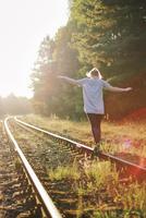 Girl balancing on a railway track.
