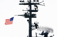 Radar and aerial masts with a United States flag.