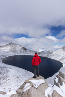 Man standing on a rock above a crater lake in winter.