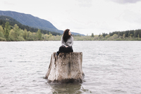 Young woman sitting on a large tree trunk in a lake.