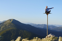 Man using his mobile phone, sitting on top of a tall pole in a mountain landscape.