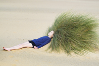 Girl lying on her back  on a sandy beach, her head in a large patch of beach-grass.