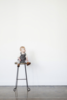 A young child, a baby girl sitting on a tall stool.