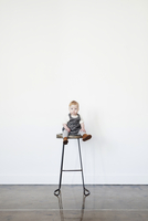 A young child, a little girl sitting on a tall stool laughing.
