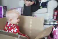 A young boy sitting in a large cardboard box, among wrapping paper and presents.