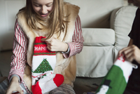 Two people unwrapping Christmas stocking presents on Christmas morning.