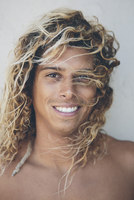 Portrait of young Hispanic surfer with bleached blonde hair.