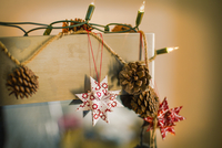 Christmas decorations. Fairy lights, pine cones and paper stars.