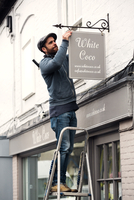 A man on a ladder fixing a painted name sign onto a bracket on a shopfront.  11093009446| 写真素材・ストックフォト・画像・イラスト素材|アマナイメージズ
