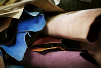 A pile of fabrics and leather heaped up in a bookbinding workshop.