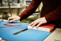 A man working on a bench, to measure and cut the material for recovering a book, in a bookbinding workshop.