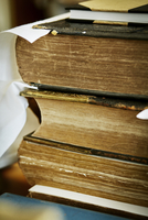 A stack of books, with yellowed worn page edges and worn bindings.