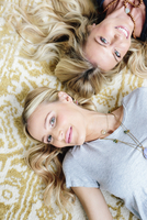 Two young woman lying on their backs, looking up at the camera. 11093009529| 写真素材・ストックフォト・画像・イラスト素材|アマナイメージズ