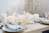 A table with lit candles, china plates and glasses.