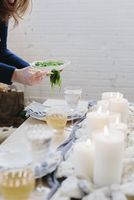 A woman placing a plate of food on a table decorated with lighted candles.  11093009594| 写真素材・ストックフォト・画像・イラスト素材|アマナイメージズ
