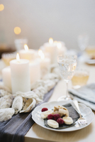 A table for a celebration meal with wine glasses filled and plates of fruit, and lit candles in the centre of the table.  11093009619| 写真素材・ストックフォト・画像・イラスト素材|アマナイメージズ
