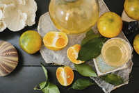 Overhead view of a table with sliced oranges and glasses.