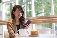 Smiling young woman sitting at a table with a mug and slice of cake, looking at her smart phone.