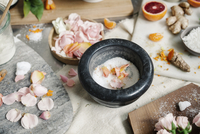 Overhead view of a pestle and mortar and rose petals, ginger and oranges
