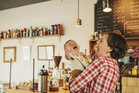 A woman holding a crying baby in a coffee shop.  11093009759| 写真素材・ストックフォト・画像・イラスト素材|アマナイメージズ
