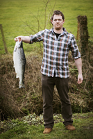 A man standing holding a large freshly caught salmon fish.