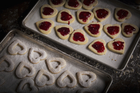 Valentine's Day baking, woman spreading raspberry jam on heart shaped biscuits.