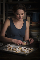 Valentine's Day baking, young woman sitting in a kitchen, with a baking tray of heart shaped biscuit. 11093010192| 写真素材・ストックフォト・画像・イラスト素材|アマナイメージズ