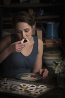 Valentine's Day baking, young woman sitting in a kitchen, eating a heart shaped biscuit. 11093010193| 写真素材・ストックフォト・画像・イラスト素材|アマナイメージズ