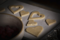 Valentine's Day baking, high angle view of heart shaped biscuits on a baking tray.