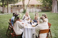 Group of female friends gathered around a table, in a garden, eating and drinking.