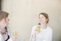 Two women sitting at a table, smiling at each other, holding glasses of champagne. 11093010543| 写真素材・ストックフォト・画像・イラスト素材|アマナイメージズ