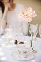 Close up of a rose in a vase on a table with a cup and saucer and glasses. 11093010556| 写真素材・ストックフォト・画像・イラスト素材|アマナイメージズ