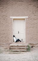 Young woman with long brown hair sitting on the ground outside the front door of a building. 11093010577| 写真素材・ストックフォト・画像・イラスト素材|アマナイメージズ