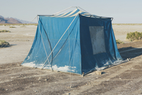 Old muddy blue camping tent in the desert of the Bonneville Salt Flats.