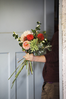 Organic flower arrangements. A woman creating a hand tied bouquet.