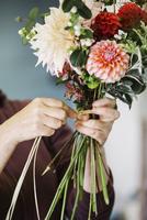 Organic flower arrangements. A woman creating a hand tied bouquet. 11093010644| 写真素材・ストックフォト・画像・イラスト素材|アマナイメージズ