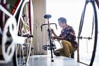 A man working in a bicycle repair shop.  11093010720| 写真素材・ストックフォト・画像・イラスト素材|アマナイメージズ