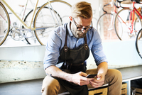 A man working in a bicycle repair shop sitting checking his phone for messages. Coffee break.