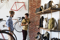 Two men in a cycle repair shop, a client looking at backpacks and bike packs.