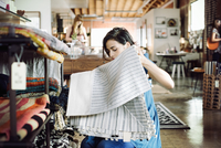 Young woman in a shop, holding a striped tablecloth.