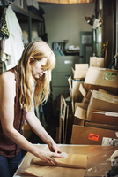 Woman with long blond hair standing in the store room of a shop, wrapping merchandise in brown paper. 11093010835  写真素材・ストックフォト・画像・イラスト素材 アマナイメージズ