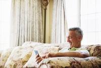 Smiling senior man sitting on a sofa, using a mobile phone. 11093010837| 写真素材・ストックフォト・画像・イラスト素材|アマナイメージズ