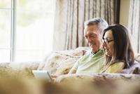 Smiling senior couple sitting on a sofa, using a laptop computer. 11093010845| 写真素材・ストックフォト・画像・イラスト素材|アマナイメージズ