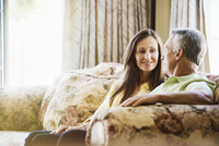 Smiling senior couple sitting on a sofa. 11093010847| 写真素材・ストックフォト・画像・イラスト素材|アマナイメージズ