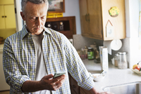 Senior man standing in a kitchen, using a mobile phone.