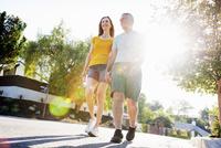 Senior couple wearing shorts walking along a street in the sunshine. 11093010883| 写真素材・ストックフォト・画像・イラスト素材|アマナイメージズ