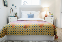 A bedroom in an apartment with a double bed and beside cabinets, and a vivid patched patterned bedspread in orange and yellow.